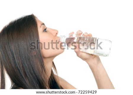 Woman drinking mineral water. Female holding in hand and drink sparkling still mineral bottled water isolated on a white background. Healthy lifestyle concept - stock photo