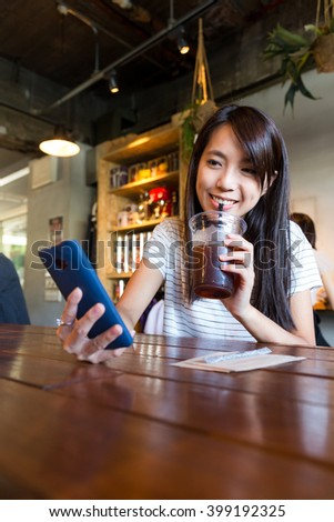 Woman drinking of coffee and look at the cellphone