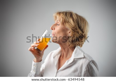 Woman drinking orange juice - stock photo