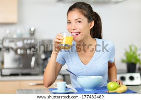 Woman drinking orange juice eating breakfast smiling happy in the morning. Beautiful young multiracial woman sitting in her kitchen at home. Mixed race Asian Caucasian female model eating healthy. - stock photo