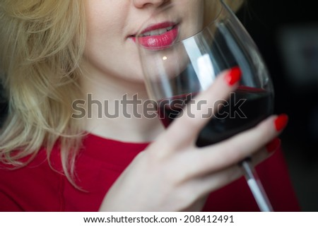 Woman drinking red wine with red lips and glass