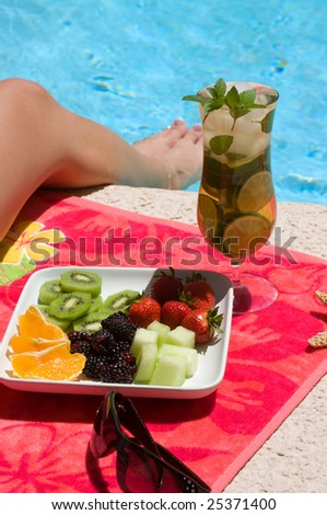Woman drinking refreshing ice tea and eating healthy fruit near the pool on a spa vacation