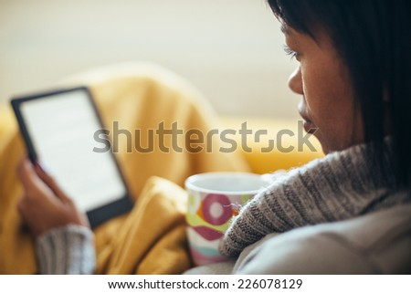 Woman drinking tea and reading book on couch - stock photo