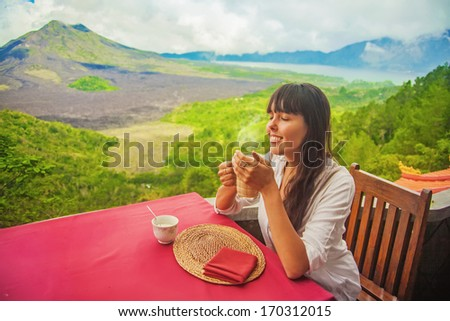 woman drinking tea at mountains in bali - stock photo