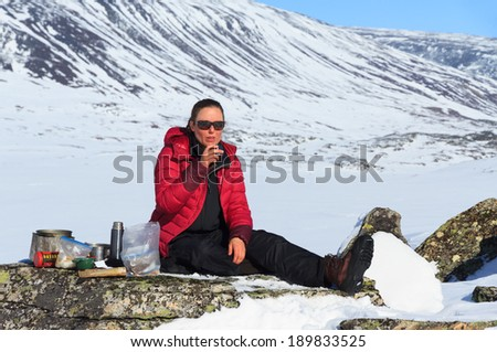 Woman drinking tea during a break of a cross country skiing tour in Lapland. - stock photo