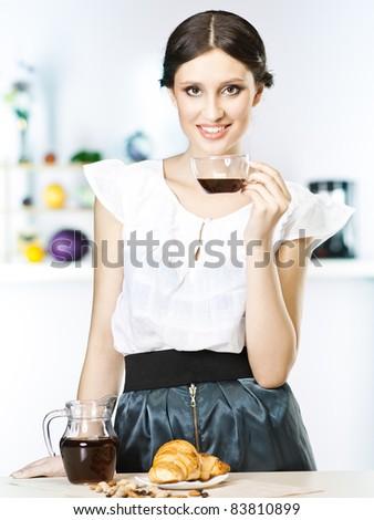 Woman drinking tea in kitchen - stock photo