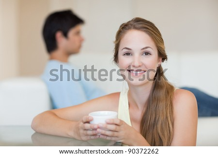 Woman drinking tea while her fiance is sitting on a couch in their living room - stock photo