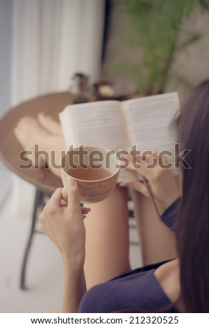 Woman drinking tea while reading a book at home, rear view - stock photo