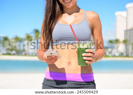 Woman drinking vegetable Green detox smoothie after fitness running workout on summer day. Fitness and healthy lifestyle concept with beautiful fit mixed race Asian Caucasian model. - stock photo