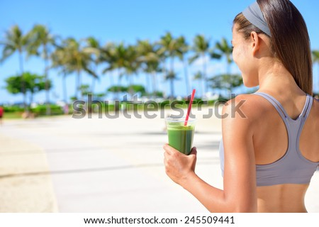 Woman drinking vegetable Green detox smoothie after fitness running workout on summer day. Fitness and healthy lifestyle concept with beautiful fit mixed race Asian Caucasian model outside on beach. - stock photo