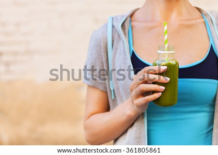 Woman drinking vegetable smoothie after fitness running workout on summer day. Fitness and healthy lifestyle concept - stock photo