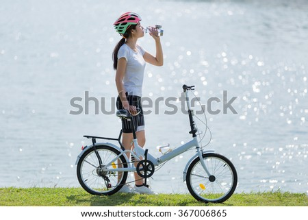 Woman drinking water after exercise bike. - stock photo