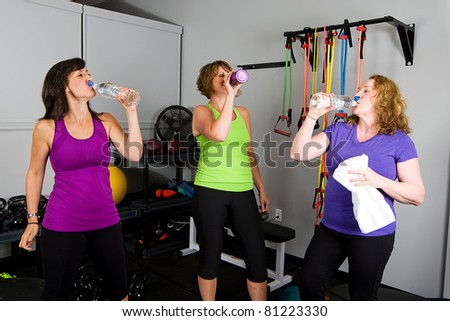woman drinking water at a gym - stock photo