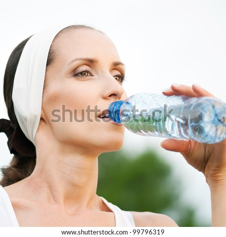 Woman drinking water at outdoors workout
