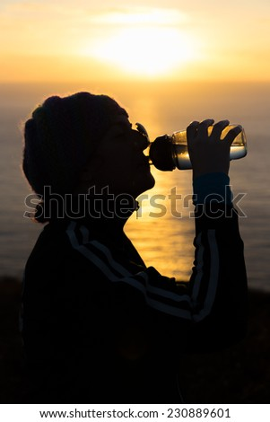 Woman drinking water from a bottle at sunrsise