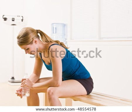 Woman drinking water in health club - stock photo