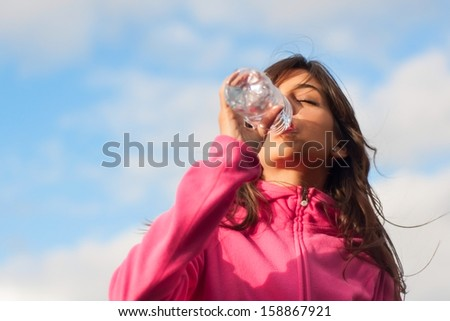 Woman drinking water outdoors with a sky and clouds background