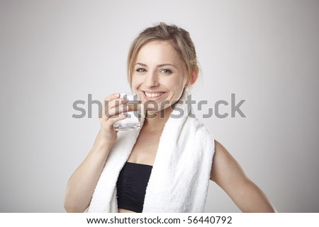 Woman Drinking Water wearing sportswear and towel - stock photo