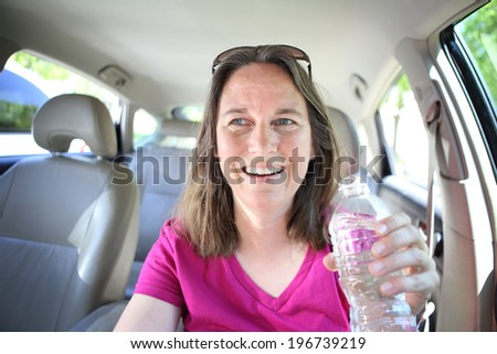 Woman drinking water while driving  - stock photo