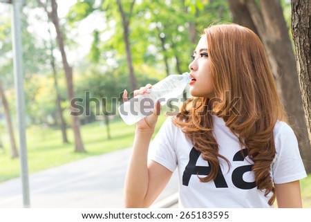 Woman drinking water while exercising in the beautiful green nature park - stock photo