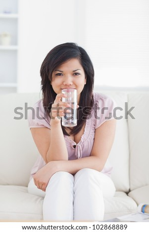 Woman drinking water while sitting in a couch in a living room - stock photo