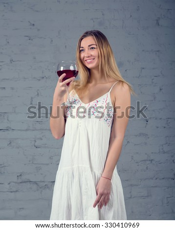Woman drinking wine. Woman and red wine. Woman with glass red wine. Woman on the brick wall background. studio photography - stock photo