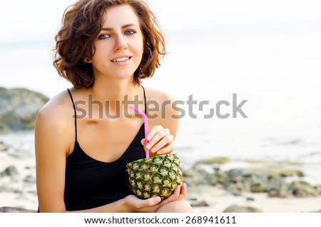 Woman drinks a cocktail from fresh pineapple - stock photo