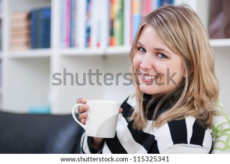 Woman drinks a cup of coffee on the couch - stock photo