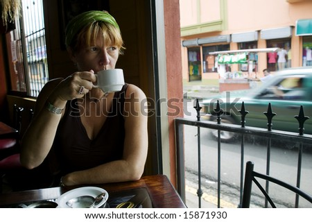 Woman drinks coffee in an Alejuela Costa Rica cafe - stock photo