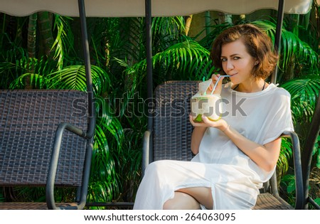 Woman drinks fresh coconut on the swinset - stock photo