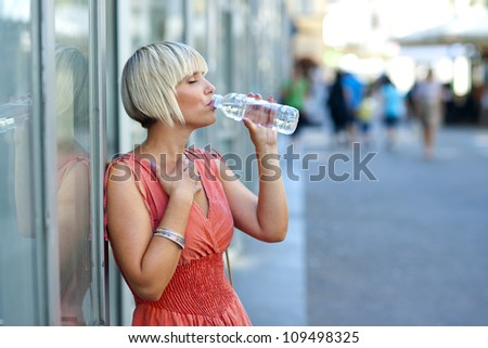 woman drinks water from bottle in the city - stock photo