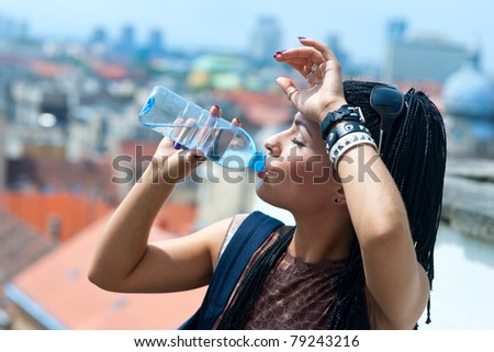 woman drinks water from plastic bottle - stock photo