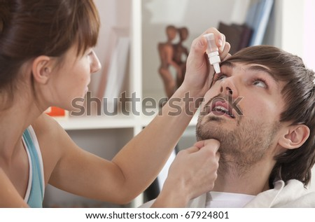 Woman dripping man eye with eyes drops - stock photo