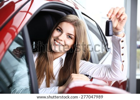 Woman Driver Holding Car Keys siting in Her New Car - stock photo