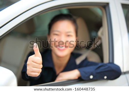 woman driver thumb up in car - stock photo