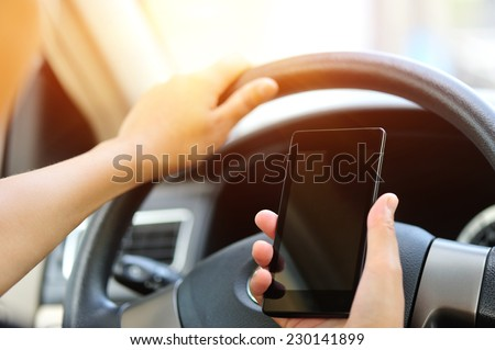 woman driver use her cell phone driving  car - stock photo