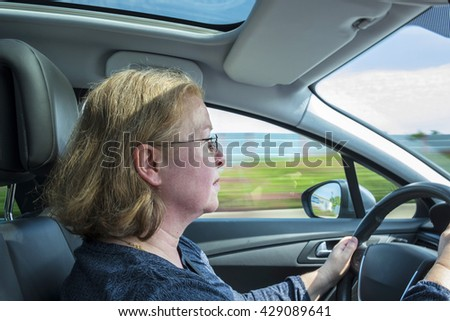 woman drives the car very concentrated on a german highway