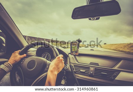Woman driving a car and using a navigation device