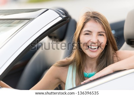 Woman driving a car looking very happy and smiling - stock photo