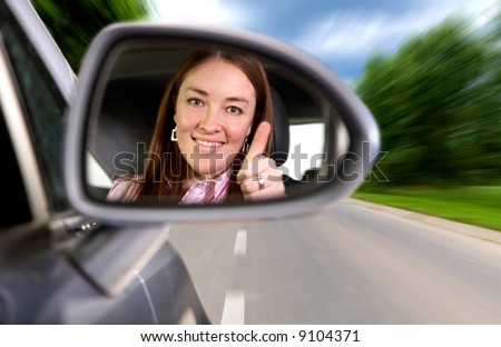 woman driving a car on a road with thumbs up in the mirror - stock photo