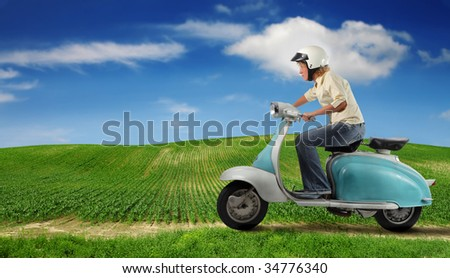 woman driving a moped in the countryside - stock photo