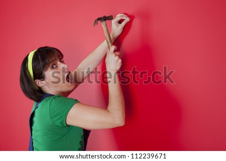 woman driving a nail in a red wall - stock photo