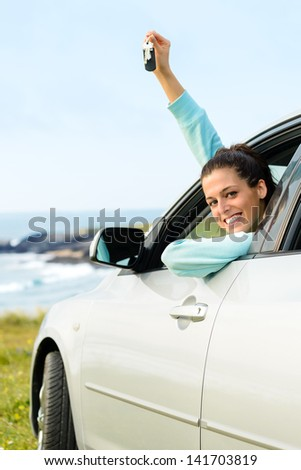 Woman driving car and holding keys on summer travel to coast. Happy female driver out of the auto window.