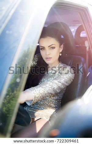 Woman driving car. Girl in party dress with golden sequins in auto. Summer vacation and travelling concept. Fashion and style. Holidays, birthday, anniversary celebration