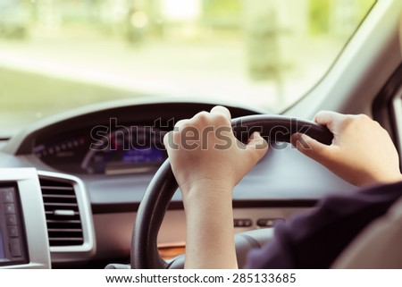 woman driving car, hand hold steering wheel - stock photo