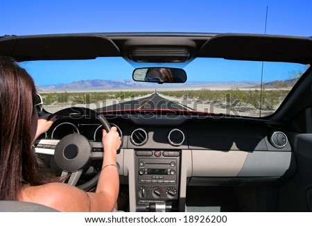 Woman driving car on empty road, Death Valley, California - stock photo
