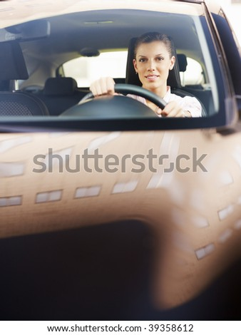 woman driving car. Reflections of building on hood. Copy space - stock photo