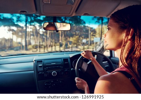 Woman driving on vacation on country road happy and smiling - stock photo