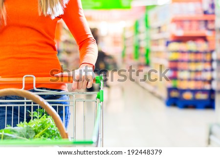 Woman driving shopping cart while grocery shopping in supermarket  - stock photo