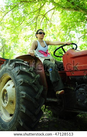 woman driving tractor - stock photo